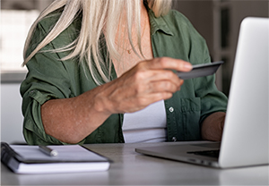 woman holding a credit card and looking at a laptop