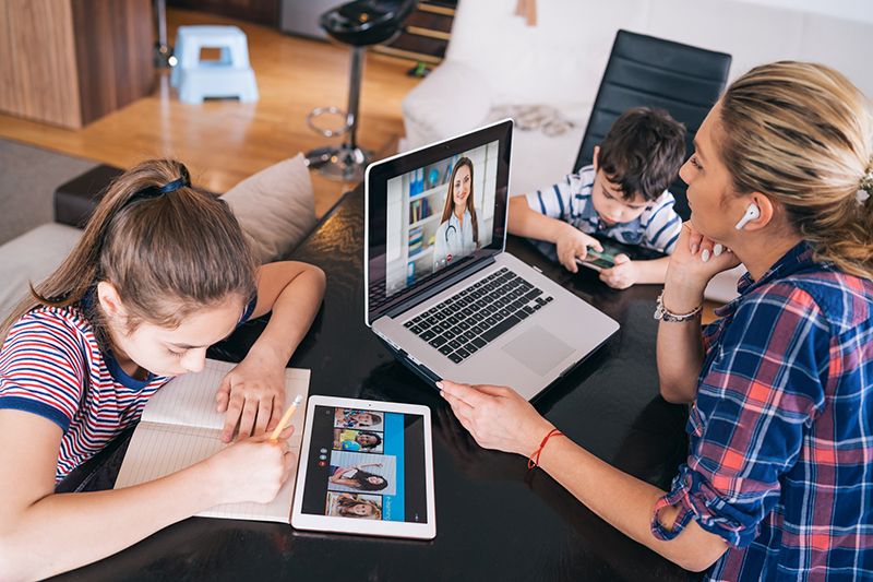 Woman on a laptop sitting next to a girl on an iPad and a young boy on a cellphone